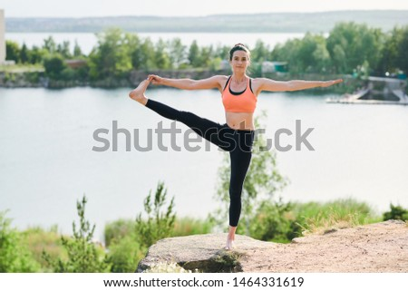 Content young woman in sports bra and leggings standing on one leg Stock photo © pressmaster