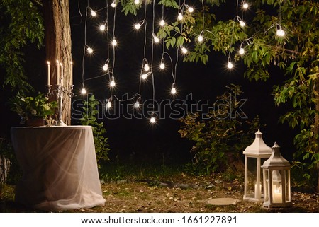night wedding ceremony. A garland of light bulbs. candles in glass flasks in the evening. Stock photo © ruslanshramko