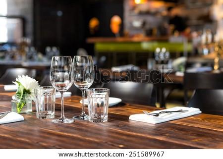 Glasses, flower fork, knife served for dinner in restaurant with cozy interior Stock photo © ruslanshramko