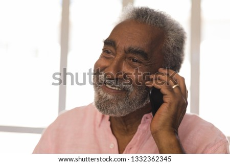 Front view of active senior man talking on mobile phone at beach. She seems happy Stock photo © wavebreak_media