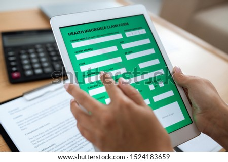 Electronic form of health insurance in digital tablet held by human hands Stock photo © pressmaster