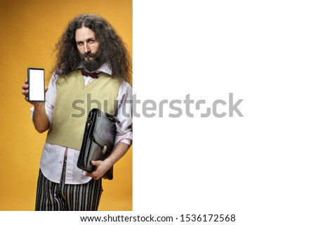 Eccentric man holding a smartphone and leaning on white board Stock photo © majdansky