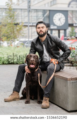 Young man in black jeans and leather jacket chilling with his pet Stock photo © pressmaster