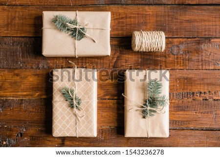 Packed and wrapped giftboxes with conifer on top and spool of threads on table Stock photo © pressmaster