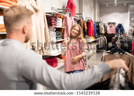Cheerful young woman holding hangers with pink pullover by chest Stock photo © pressmaster