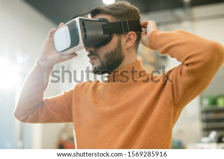 Casual guy putting vr goggle on head to find himself in virtual shop Stock photo © pressmaster