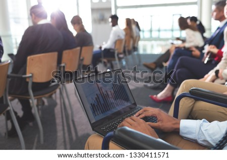 Mid section of disabled young African american businessman using laptop during seminar in office bui Stock photo © wavebreak_media