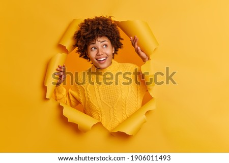 Pleased dreamy woman with curly hairstyle, looks through transparent glasses, dressed in casual whit Stock photo © vkstudio