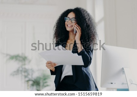 Pleased successful businesswoman with Afro hairstyle wears spectacles to provide eyes protection, ho Stock photo © vkstudio