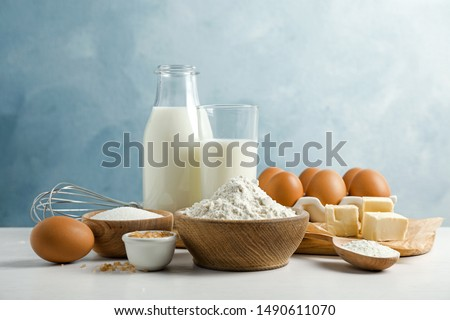 Baking ingredients on white table. Eggs, milk and flour in containers. Beater for whisking and makin Stock photo © vkstudio