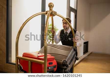 Elegant porter in eyeglasses pushing cart with pile of suitcases inside hotel Stock photo © pressmaster