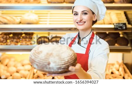 Verkoopster schort presenteren vers brood bakkerij Stockfoto © Kzenon