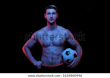 Young serious shirtless football player with soccer ball standing in isolation Stock photo © pressmaster