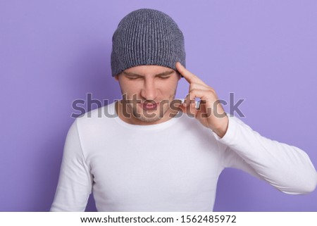 Indoor shot of attractive male keeps fingers on temples, tries to concentrate on some problem, recol Stock photo © vkstudio