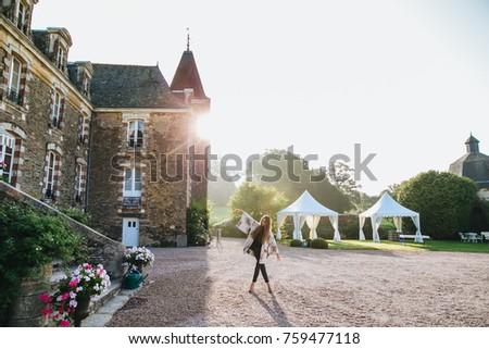 Carefree restful female model stands crossed legs feels enjoyment, poses against ancient huge castle Stock photo © vkstudio
