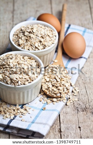 Fresh chicken eggs, oat flakes in ceramic bowl and wooden spoon  Stock photo © marylooo