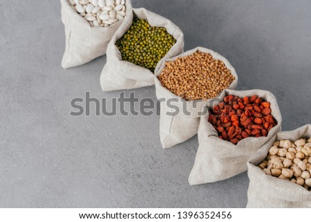 Assorted gluten free grains in linen cloth bags on grey background. Sacks filled with kidney bean, l Stock photo © vkstudio