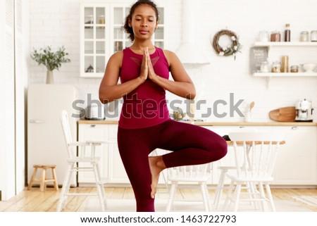 Young beautiful woman doing yoga asana Tree Pose in dark room Stock photo © GVS
