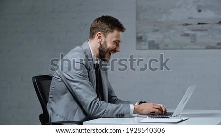Imagen satisfecho barbado empresario usando la computadora portátil pie Foto stock © deandrobot