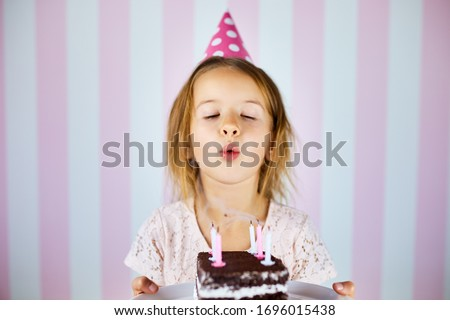 Little girl in pink birthday cap with chocolate birthday cake with candles. Stock photo © Illia
