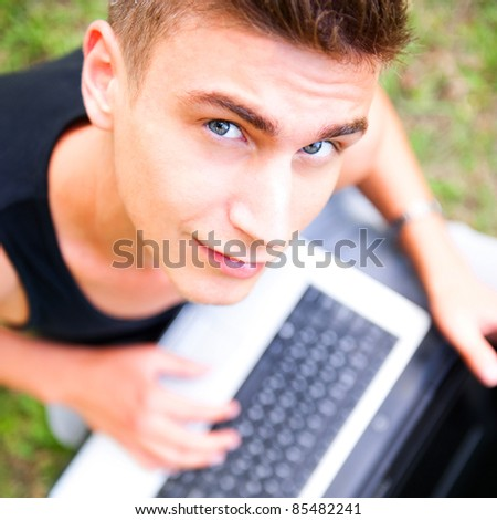 Closeup portrait of young student man using laptop and 3g usb mo Stock photo © HASLOO