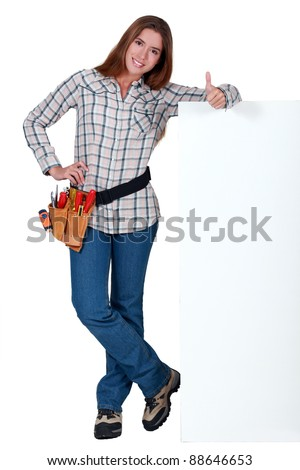 Handywoman standing next to a blank sign and giving the thumb's up Stock photo © photography33