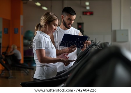 blonde middle aged woman on treadmill coached by physiotherapist stock photo © photography33