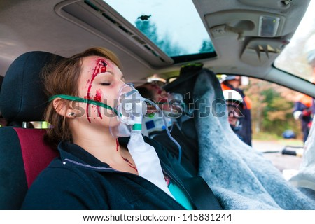 Car accident - Victims in crashed vehicle receiving first aid Stock photo © Kzenon