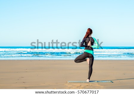young woman practicing yoga on the beach at sunset behind the ke stock photo © hasloo