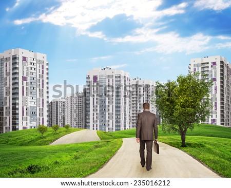 businessman walking along road through green hills city of tall buildings as backdrop charts and o stock photo © cherezoff