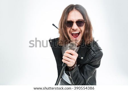 attractive young male singer with long hair singing using microphone stock photo © deandrobot