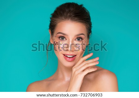 Beauty portrait of cheerful young woman with blue glitter makeup Stock photo © deandrobot