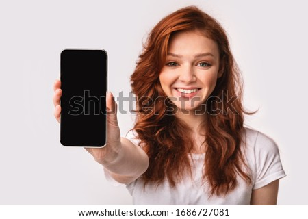 Smiling young woman showing blank screen mobile phone to camera Stock photo © deandrobot