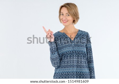smiling blonde business woman pointing away and looking at camera stock photo © deandrobot