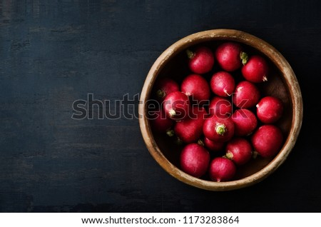 Radishes Filling Old Wooden Bowl on Grungy Black Surface from Ab Stock photo © frannyanne