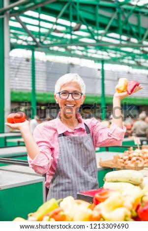 Stockfoto: Good Looking Senior Woman Wearing Glasses Sells Pepper On Marke