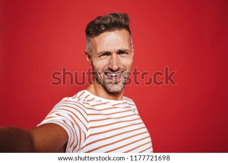 Handsome guy 30s in striped t-shirt smiling while taking selfie  Stock photo © deandrobot
