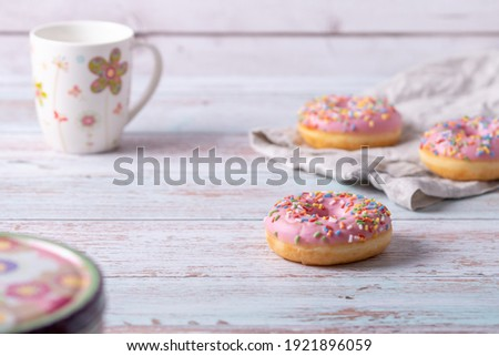 Stock photo: Delicious glazed donuts and cup of coffee on light wooden backgr