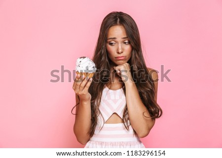 photo of upset woman 20s wearing dress holding cupcake isolated stock photo © deandrobot