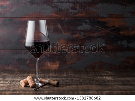 Elegant glass of red wine with box of corks and opener on stone kitchen table background. Stock photo © DenisMArt