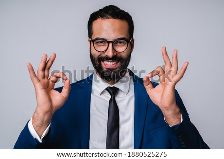 image of attractive businessman 30s in formal suit showing thumb stock photo © deandrobot