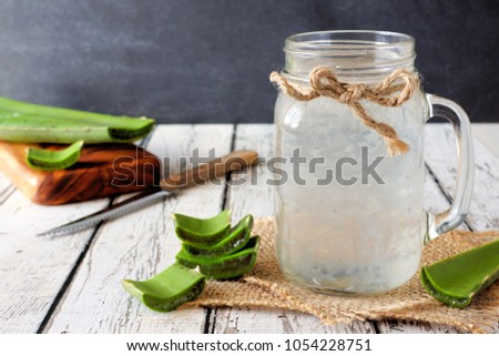 Stock photo: Aloe vera gel in a glass jar, with fresh aloe vera plant in the background