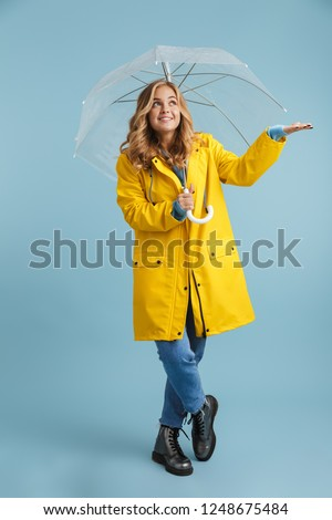 Image of young blond woman 20s wearing raincoat standing under t Stock photo © deandrobot