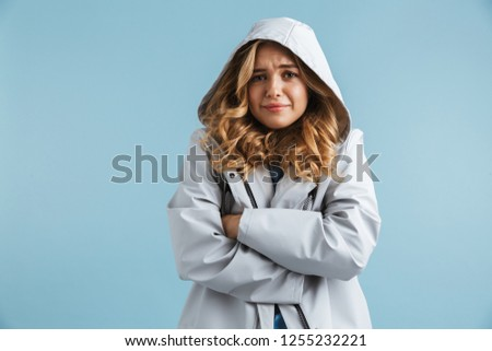 Image of displeased woman 20s wearing raincoat standing under tr Stock photo © deandrobot