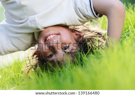 portraits of happy kids playing upside down outdoors in summer park walking on hands stock photo © galitskaya