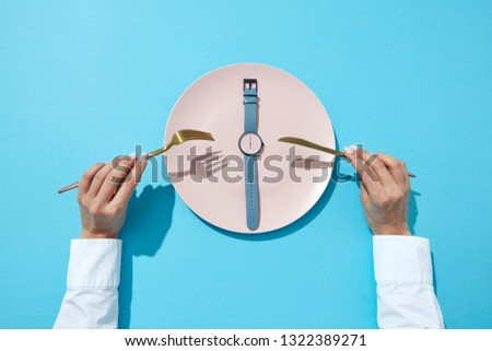 White plate with whatch shows six o'clock served knife and fork on a blue background and shadows. Ti Stock photo © artjazz