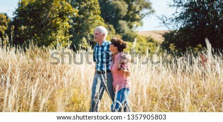senior man and woman enjoying themselves and nature having walk stock photo © kzenon