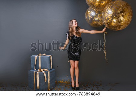 Gorgeous blonde woman in elegant black dress smiling at camera. Stock photo © studiolucky