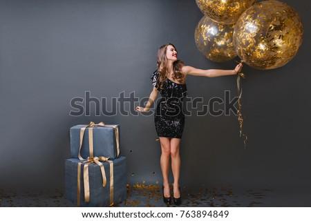 Gorgeous blonde woman in elegant black dress smiling at camera. stock photo © studiolucky