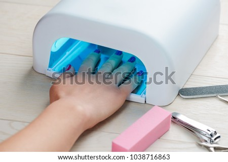 Woman Hands Care. Manicured nails in UV lamp. Rays cure gel polish. Small nail art and manicure busi stock photo © galitskaya